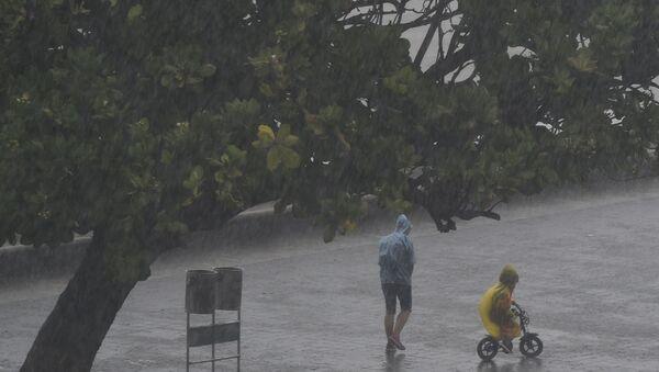 People walk under the rain along Marine Drive as rain falls in Mumbai on June 4, 2020, the day after cyclone Nisarga's landfall in India's western coast.  - Sputnik International