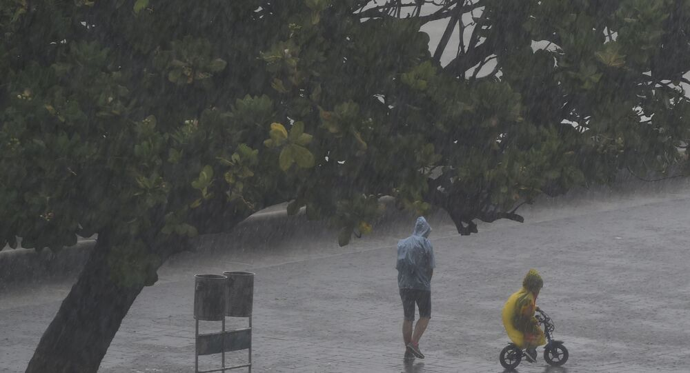 People walk under the rain along Marine Drive as rain falls in Mumbai on June 4, 2020, the day after cyclone Nisarga's landfall in India's western coast.