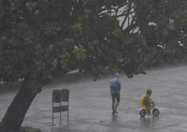 People walk under the rain along Marine Drive as rain falls in Mumbai on June 4, 2020, the day after cyclone Nisarga's landfall in India's western coast.
