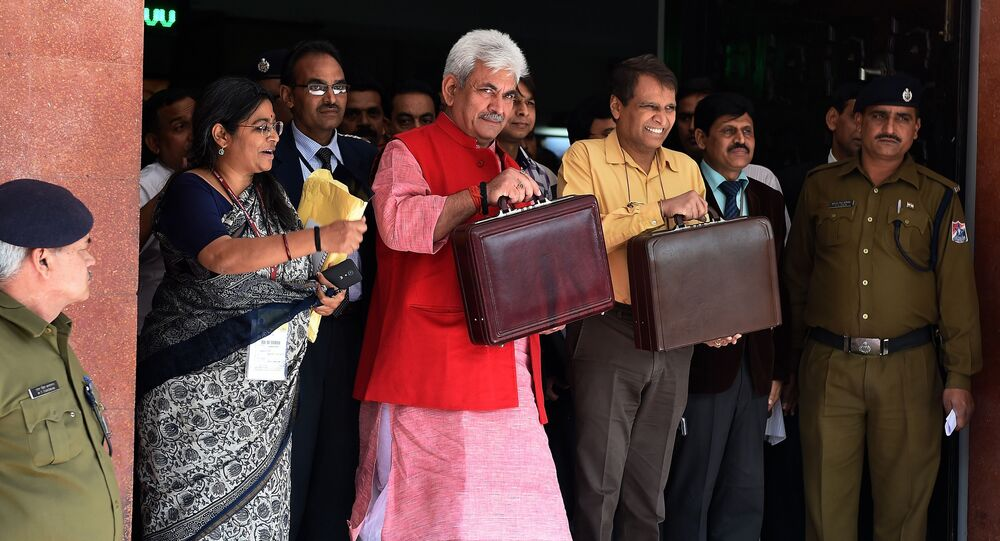Indian Railways Minister Suresh Prabhu (3R) leaves his office with Minister of State for Railways, Manoj Sinha (C/RED) for the Indian parliament to present the railway budget in New Delhi on February 26, 2015