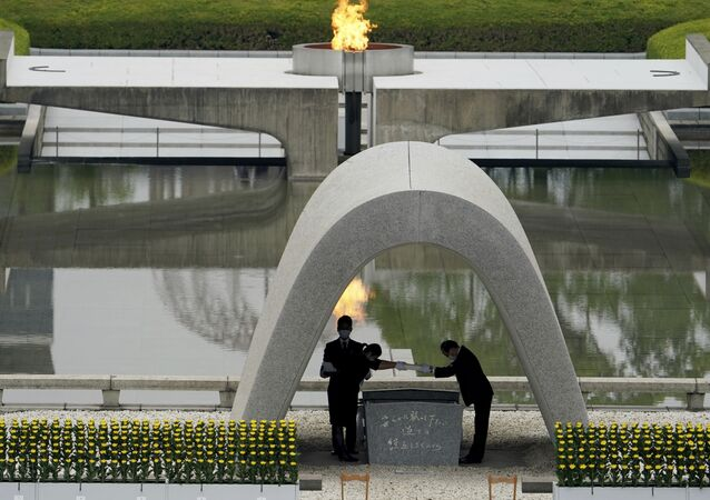 Kazumi Matsui, right, mayor of Hiroshima, and the family of the deceased bow before they place the victims list of the Atomic Bomb at Hiroshima Memorial Cenotaph during the ceremony to mark the 75th anniversary of the bombing at the Hiroshima Peace Memorial Park Thursday, Aug. 6, 2020, in Hiroshima, western Japan.