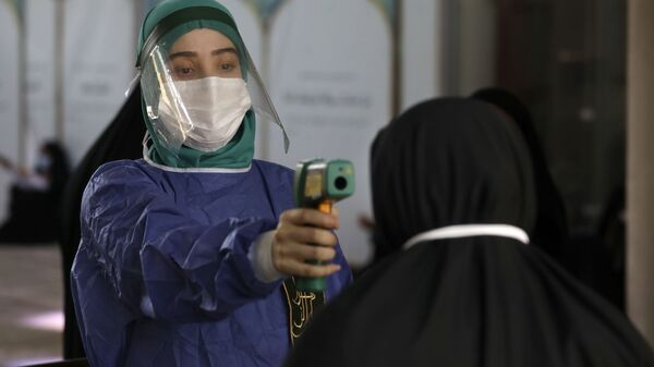 A volunteer wearing protective gear to help prevent the spread of the coronavirus checks temperature of a worshipper as she enters mosque of Tehran University to pray during Arafat Day, Iran, Thursday, July 30, 2020 - Sputnik International