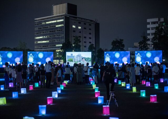 Visitors watch a screen (back C) displaying virtual lanterns as paper lanterns are placed to mark the 75th anniversary of the atomic bombing, at a park in in Hiroshima on August 6, 2020. - Japan on August 6, 2020 marked 75 years since the world's first atomic bomb attack, with the COVID-19 coronavirus pandemic forcing a scaling back of annual ceremonies to commemorate the victims.