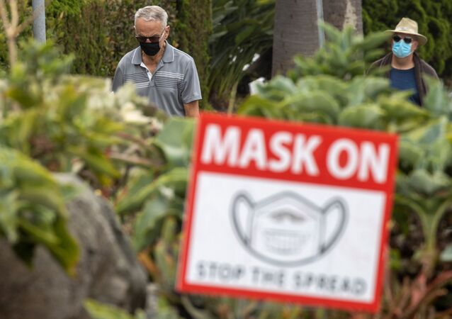 People wear masks as they walk along the pavement during the coronavirus disease (COVID-19) outbreak in Del Mar, California,30 July 2020.