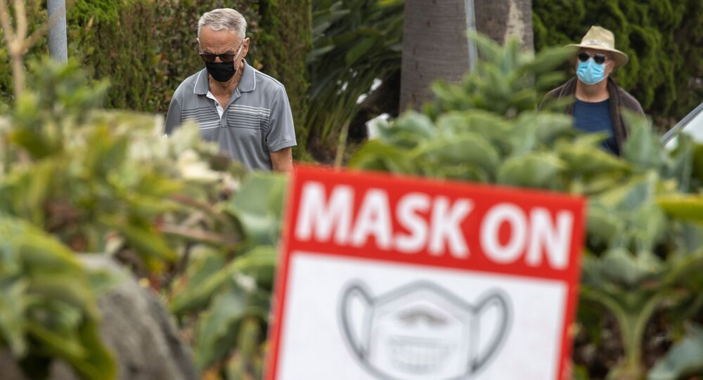 People wear masks as they walk along the side walk during the outbreak of the coronavirus disease (COVID-19) in Del Mar, California, U.S., July 30, 2020.