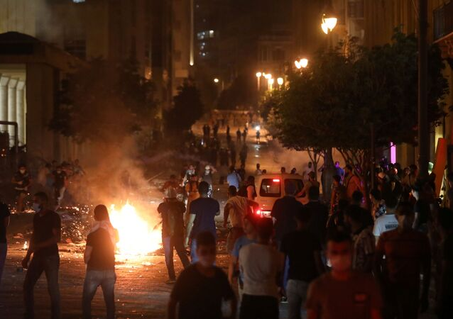 Demonstrators stand near burning fire during a protest near parliament, following Tuesday's blast in Beirut's port area, Lebanon August 7, 2020.