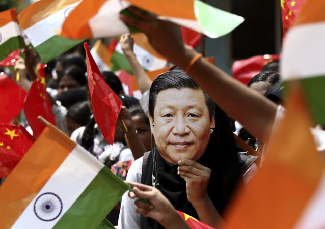 FILE- In this 10 October 2019 file photo, an Indian schoolgirl wears a face mask featuring Chinese President Xi Jinping to welcome him on the eve of his visit in Chennai, India
