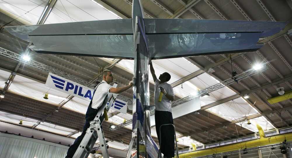 Workers are seen by a Pilatus PC-12 aircraft, during preparations for the upcoming European Business Aviation Convention & Exhibition, EBACE, at the Geneva Palexpo , Geneva, Switzerland,  Monday, May 19, 2008