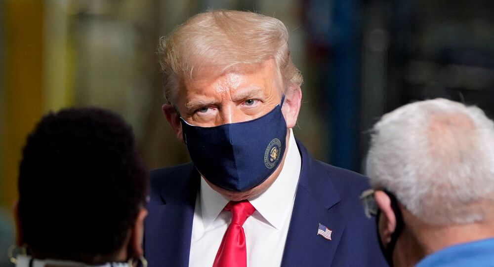 US President Donald Trump wears a protective face mask due to the coronavirus disease (COVID-19) pandemic as he talks with workers while touring a Whirlpool Corporation washing machine factory in Clyde, Ohio, US, 6 August 2020