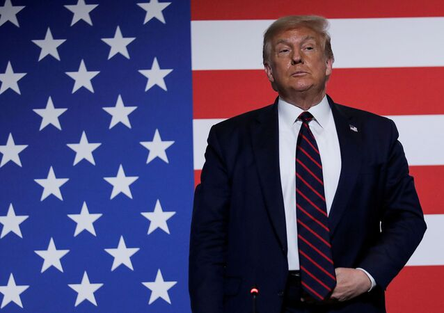U.S. President Donald Trump stands in front of a U.S. flag as he participates in a roundtable on donating plasma during a visit to the American Red Cross National Headquarters in Washington, U.S., July 30, 2020