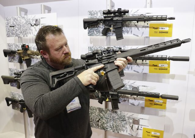 Bryan Oberc, Munster, Ind., tries out an AR-15 from Sig Sauer in the exhibition hall at the National Rifle Association Annual Meeting in Indianapolis, Saturday, April 27, 2019