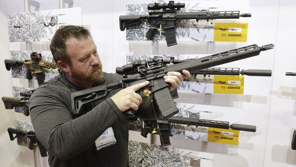 Bryan Oberc, Munster, Ind., tries out an AR-15 from Sig Sauer in the exhibition hall at the National Rifle Association Annual Meeting in Indianapolis, Saturday, April 27, 2019 - Sputnik International
