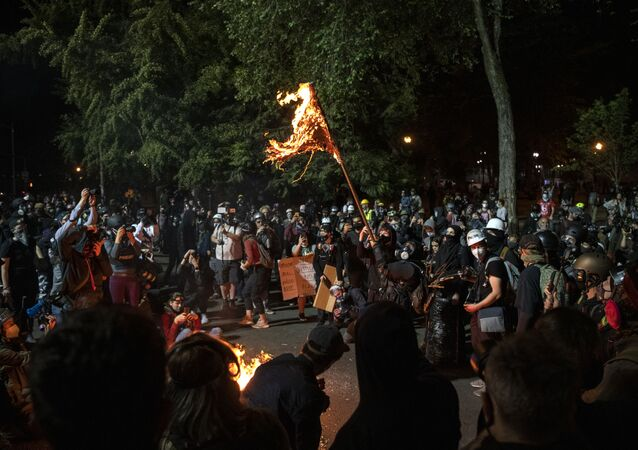 A demonstrator burns an American flag outside the Mark O. Hatfield United States Courthouse late Friday night during the protest on July 31, 2020 in Portland, Oregon.