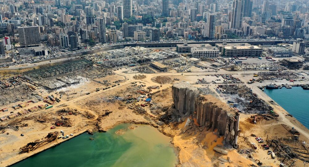 An aerial view taken on August 7, 2020, shows a partial view of the port of Beirut, the damaged grain silo and the crater caused by the colossal explosion three days earlier of a huge pile of ammonium nitrate that had languished for years in a port warehouse, leaving scores of people dead or injured and causing devastation in the Lebanese capital. The city of Beirut can be seen in the background.