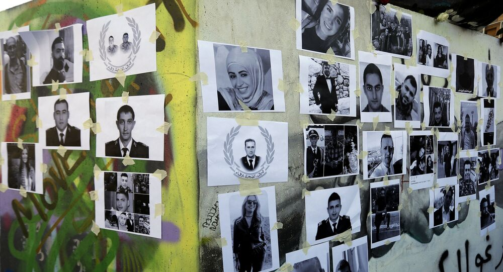 Pictures of Beirut port blast victims are plastered on the base of the Martyr's statue in Beirut Martyr's Square on August 7, 2020.