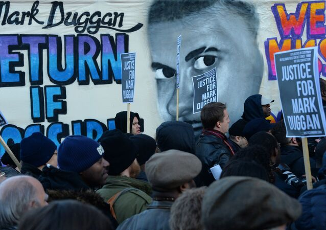 People stand beside a banner depicting Mark Duggan, who was shot dead by police, outside Tottenham Police Station in London on January 11, 2014, during a vigil following a jury verdict on January 8, 2014 ruling that Mark Duggan was lawfully killed when he was shot dead by police in August 2011.