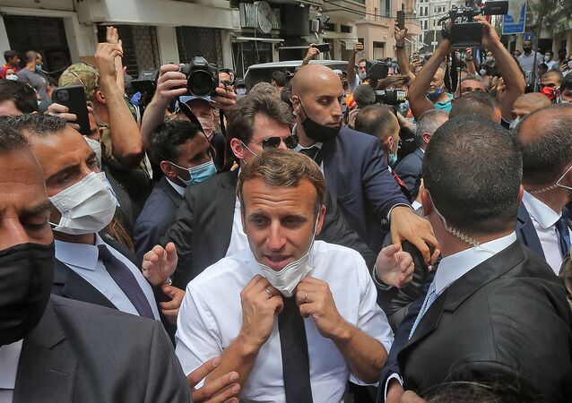 French President Emmanuel Macron adjusts his protective mask as he visits the Gemmayzeh neighbourhood which has suffered extensive damage due to a massive explosion in the Lebanese capital, on August, 6. 2020.