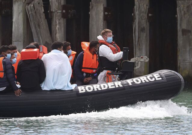 A British Border Force vessel carries a group of men thought to be migrants into Dover harbour, Southern England, Tuesday Aug. 4, 2020.