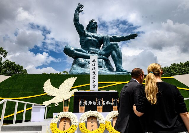 People stand in front of the cenotaph and the Peace statue after the ceremony marking the 75th anniversary of the atomic bombing of Nagasaki, at the Nagasaki Peace Park on August 9, 2020.