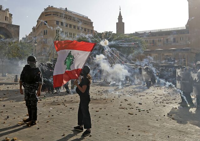 A Lebanese protester waves the national flag during clashes with security forces in downtown Beirut on August 8, 2020, following a demonstration against a political leadership they blame for a monster explosion that killed more than 150 people and disfigured the capital Beirut.