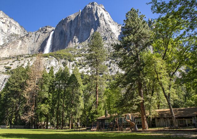 In this May 27, 2020, photo provided by the National Park Service, Yosemite Valley School, lower right, stands in Yosemite National Park, Calif. In the background is Upper Yosemite Falls.