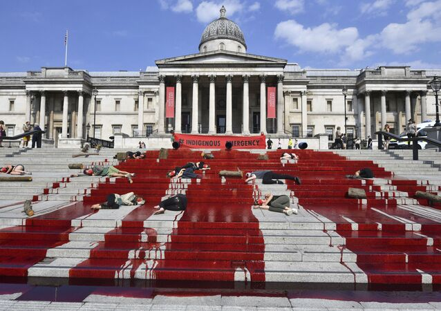 Red dye covers the steps outside the National Gallery of art as Extinction Rebellion protesters symbolically play dead, in a solidarity action for indigenous communities in Brazil