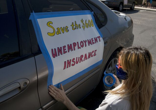 Francis Stallings tapes signs to her car before participating in a caravan rally down the Las Vegas Strip in support of extending the $600 unemployment benefit, August 6, 2020 in Las Vegas, Nevada.