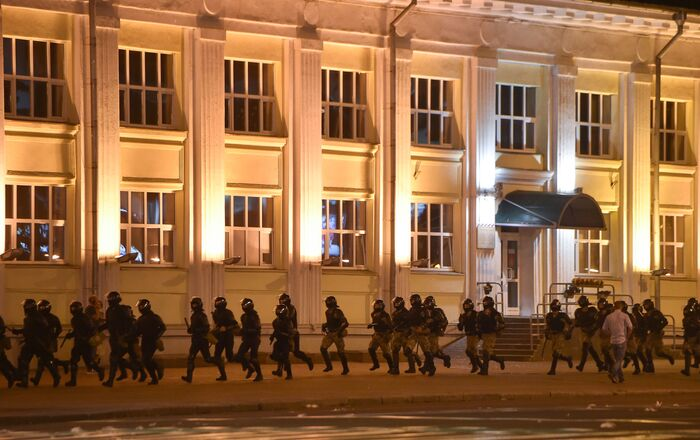 Riot police run as opposition supporters protest after polls closed in Belarus' presidential election, in Minsk on August 9, 2020.