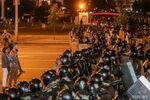 Opposition supporters stay in front of law enforcement officers blocking a street after poll closed at presidential election in Minsk, Belarus, August 9, 2020.