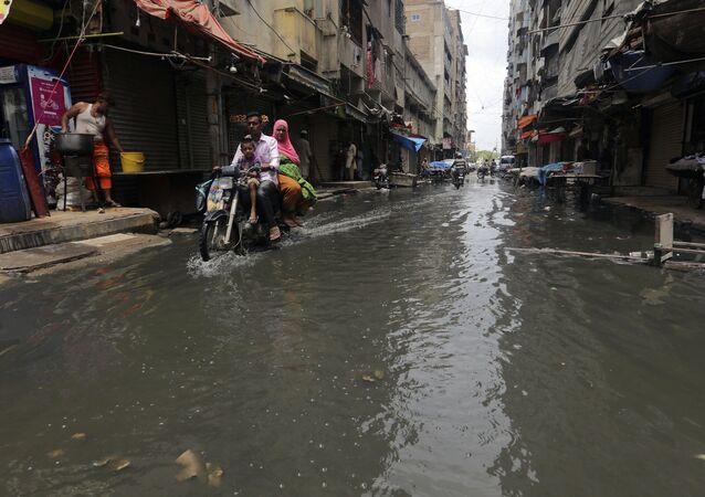 A motorcyclist drives through a street flooded by heavy rainfall in Karachi, Pakistan, Sunday, Aug. 9, 2020