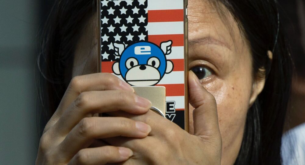 A woman takes a photo with a phone that has a United States flag themed cover outside the United States Consulate in Chengdu in southwest China's Sichuan province on Sunday, July 26, 2020