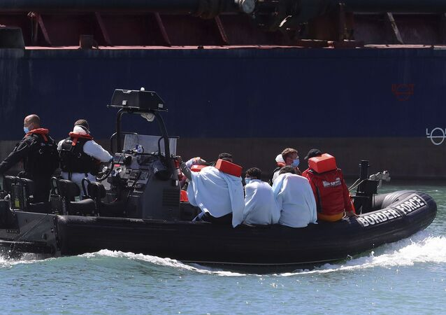 A British Border Force vessel carries a group of men thought to be migrants into Dover harbour, Southern England, Tuesday Aug. 4, 2020
