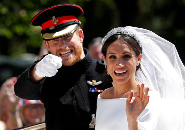 Britain's Prince Harry gestures next to his wife, Meghan, as they ride a horse-drawn carriage after their wedding ceremony at St George's Chapel in Windsor Castle in Windsor, Britain, May 19, 2018