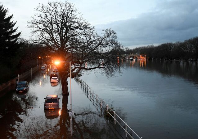 Cars are surrounded by water on a flooded road beside the River Thames in west London, Britain