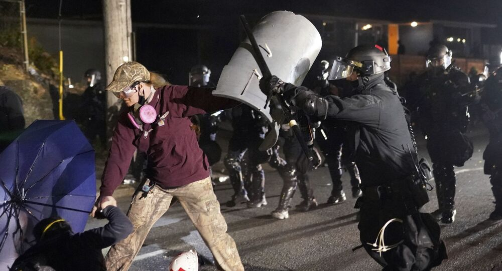 A Portland police officer shoves a protester as police try to disperse the crowd in front of the Multnomah County Sheriff's Office early in the morning on Saturday, Aug. 8, 2020 in Portland, Ore.