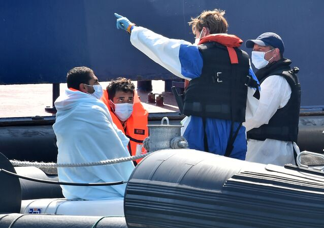 Migrants (L), believed to have been picked up from boats in the Channel, are given instructions by Border Force officials on-board Coastal patrol vessel HMC Hunter, in the port of Dover, on the south-east coast of England on 9 August 2020.