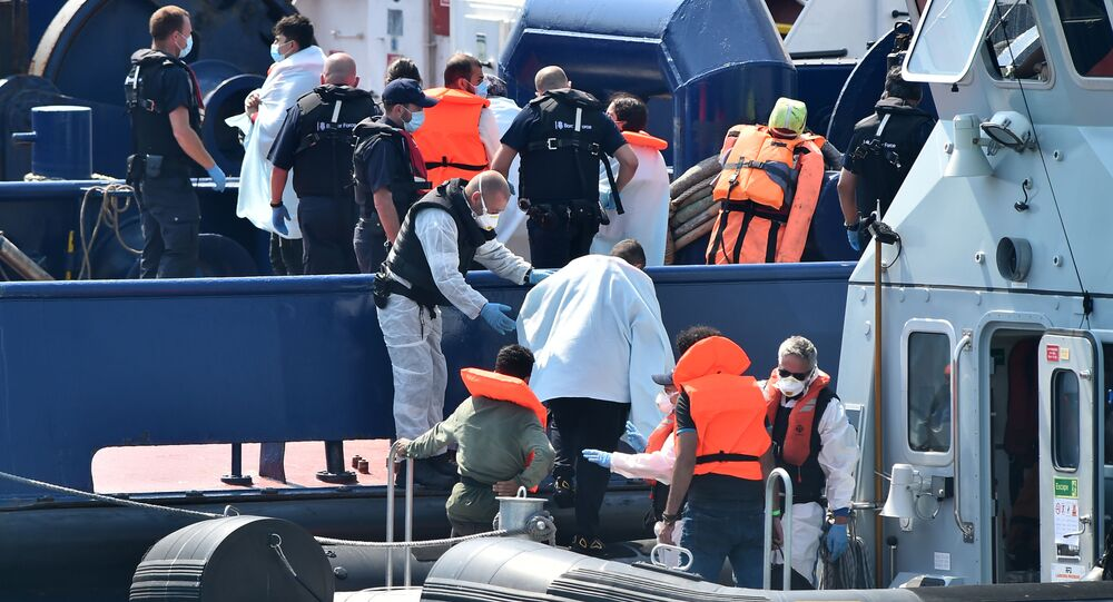 UK Border Force officers help migrants, believed to have been picked up from boats in the Channel, disembark from the coastal patrol vessel HMC Speedwell, in the port of Dover, on the south-east coast of England on 9 August 2020. (Photo by Glyn KIRK / AFP)