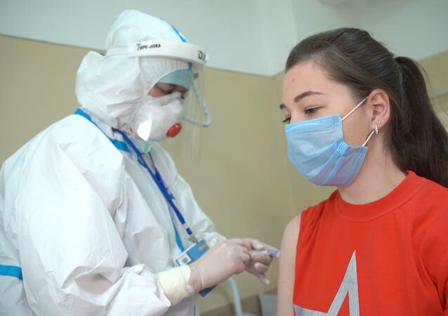 In this handout photo released by the Russian Defence Ministry, a medical worker wearing protective gear conducts daily rounds with a participant in a coronavirus vaccine trial during tests at the Burdenko Main Military Clinical Hospital in Moscow, Russia