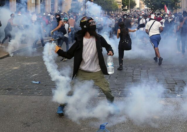 Protesters throw back tear gas canisters towards riot policemen during an anti-government protest, in the aftermath of last Tuesday's massive explosion which devastated Beirut, Lebanon, Monday, Aug. 10, 2020