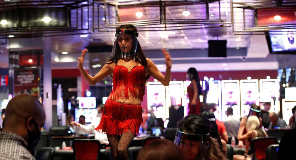 FILE PHOTO: A woman wears a face shield as she dances behind blackjack tables during the reopening of The D hotel-casino, in downtown Las Vegas, Nevada, U.S. June 4, 2020