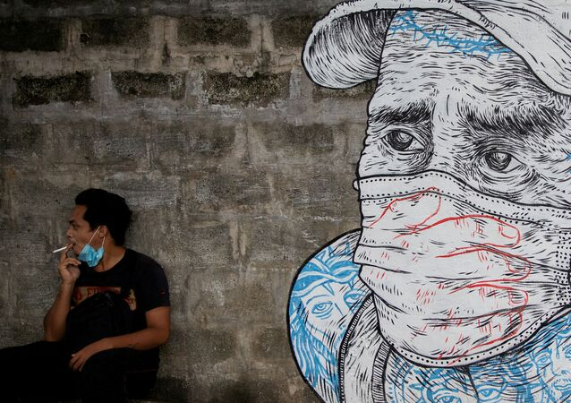 A man smokes a cigarette next to a mural of a man wearing a protective mask amid the coronavirus disease (COVID-19) outbreak in Quezon City, Metro Manila, Philippines, July 30, 2020.