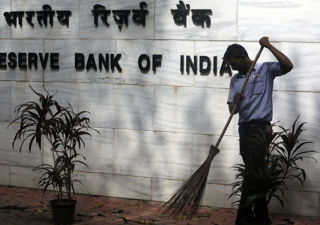 A sweeper cleans the street outside the Reserve Bank of India's headquarters in Mumbai, India, Wednesday, Aug. 2, 2017.