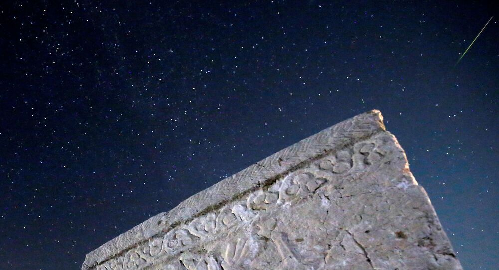 A meteor streaks past stars in the night sky above medieval tombstones during the Perseid meteor shower in Radimlja near Stolac, Bosnia and Herzegovina, August 12, 2020