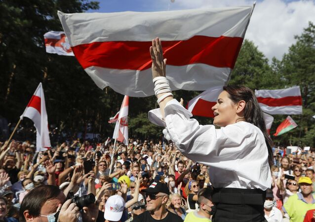 Opposition candidate Sviatlana Tsikhanouskaya greets people waving old Belarus flags during a meeting in the Belarusian city of Brest.