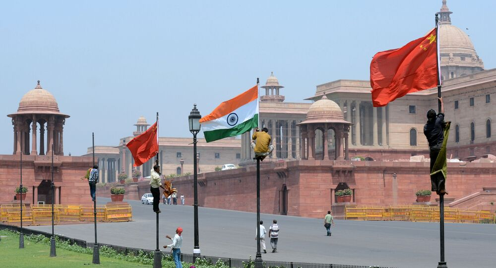 Indian workers tie Indian and Chinese national flags onto poles in front of The Indian Secretariat in New Delhi (File)