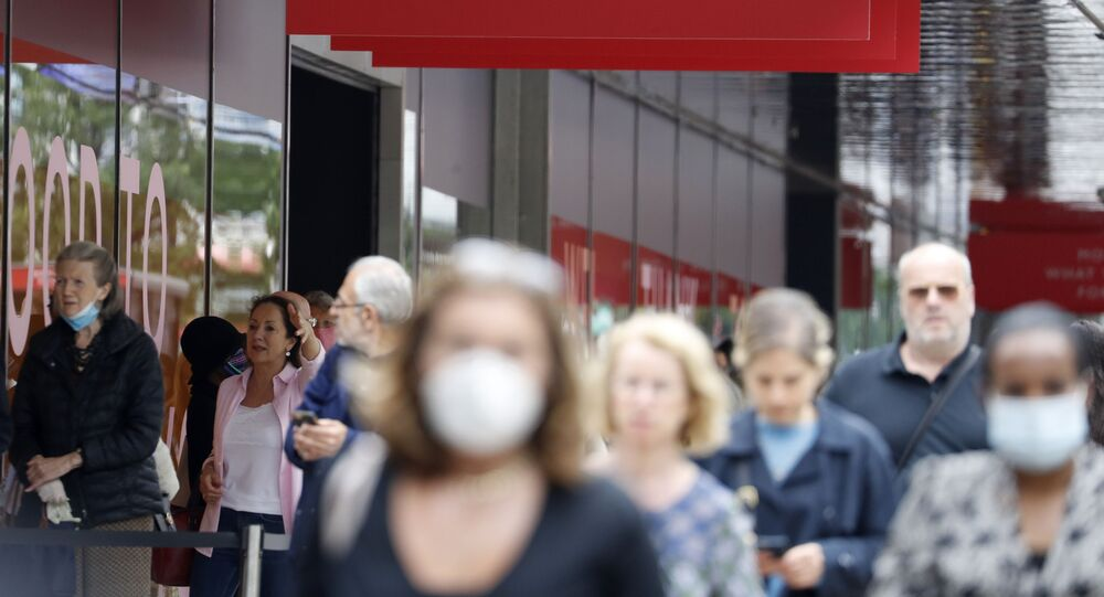 People, some wearing masks queue outside a John Lewis store, in London, Thursday, July 16, 2020. Unemployment across the U.K. has held steady during the coronavirus lockdown as a result of a government salary support scheme, but there are clear signals emerging that job losses will skyrocket over coming months