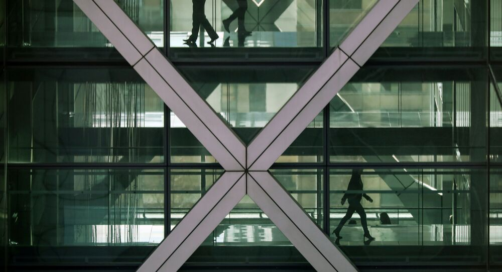 FILE PHOTO: People walk in an office in the financial centre of Canary Wharf in London, Britain March 6, 2020