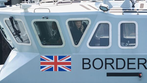 An officer looks out of a window at Dover harbour from a Border Force boat, in Dover, Britain August 11, 2020.  - Sputnik International