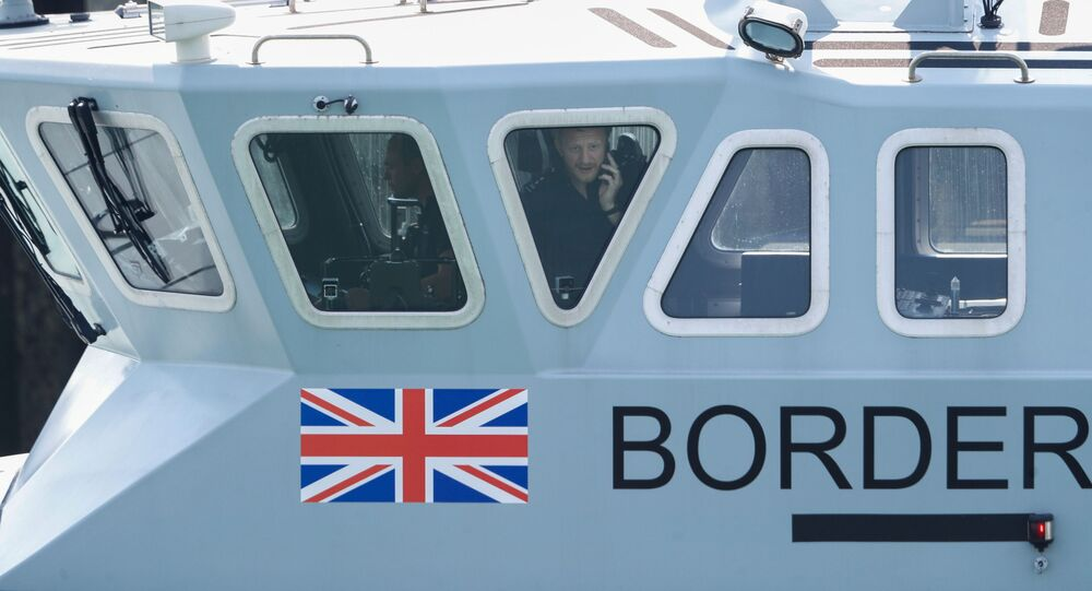 An officer looks out of a window at Dover harbour from a Border Force boat, in Dover, Britain August 11, 2020.