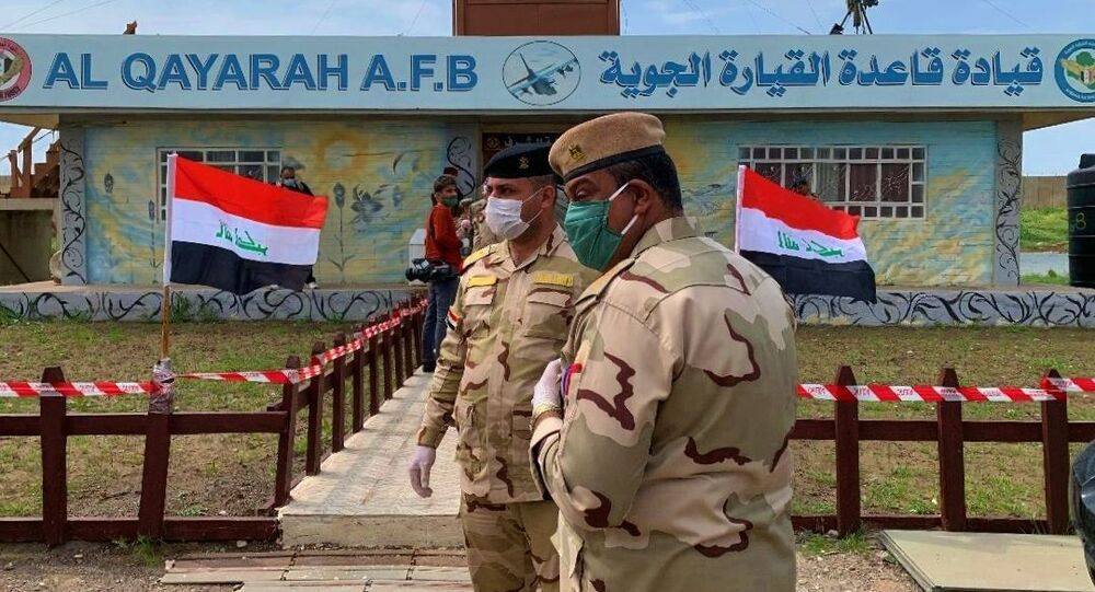 Iraqi. soldiers stand guard during the hand over ceremony of Qayyarah Airfield, Iraqi Security Forces, in the south of Mosul, Iraq early Friday, March 27, 2020. Iraq's military on Thursday said at least two rockets hit inside Baghdad's heavily fortified Green Zone, the seat of Iraq's government and home to the American Embassy, in the first attack following a brief lull in violence from earlier this month